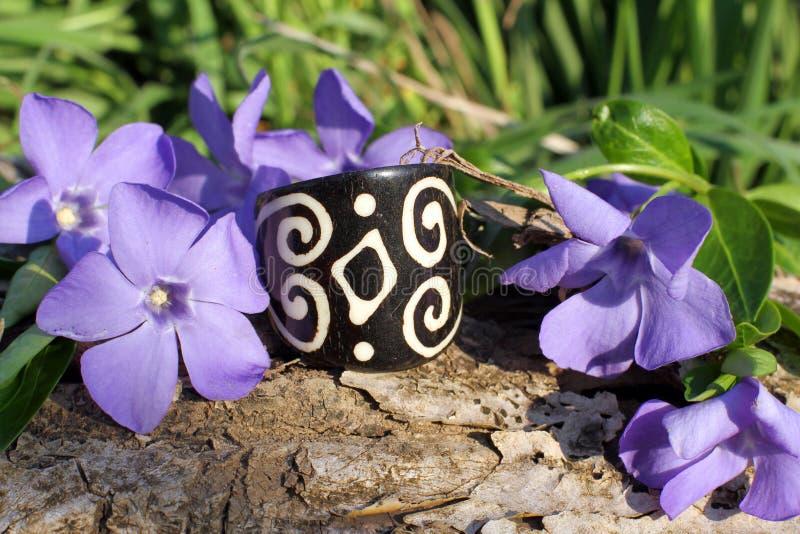 Handmade bone black ring on the nature background. Handmade bone black ring with wood violet in spring on the nature background royalty free stock photography