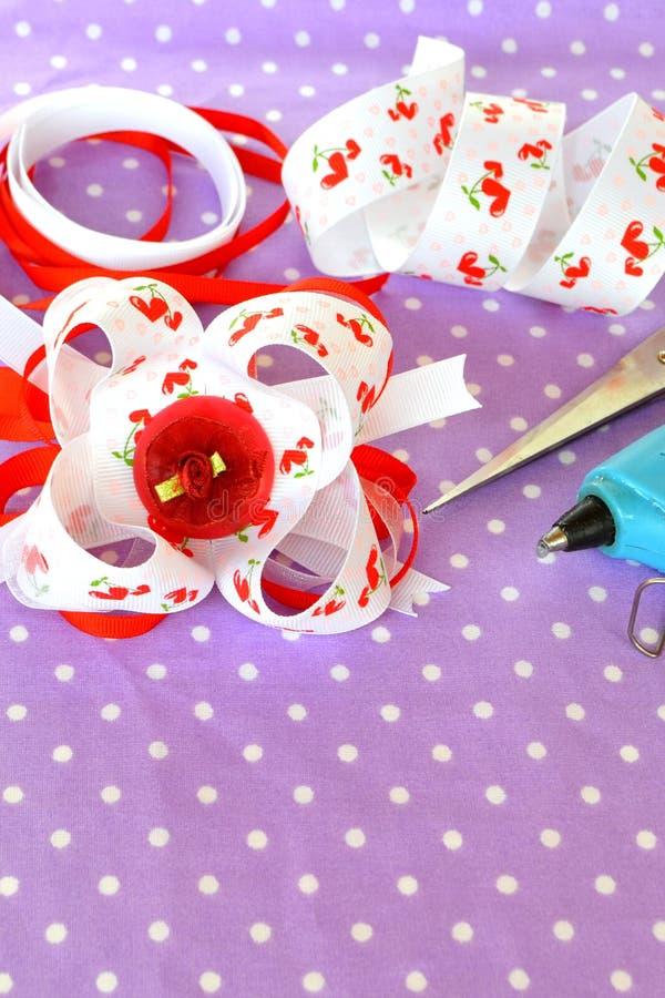 Handmade bow of ribbon, children hair accessory, ribbon set, scissors, glue gun. Simple crafts made from ribbons. Beautiful DIY ribbon idea. Girl bow idea. Girl royalty free stock images