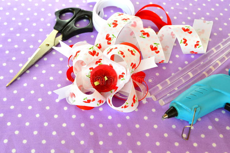 Handmade bow of ribbon, children hair accessory, ribbon set, scissors, hot adhesive gun with rod. Simple crafts made from ribbons. Beautiful DIY ribbon idea royalty free stock images