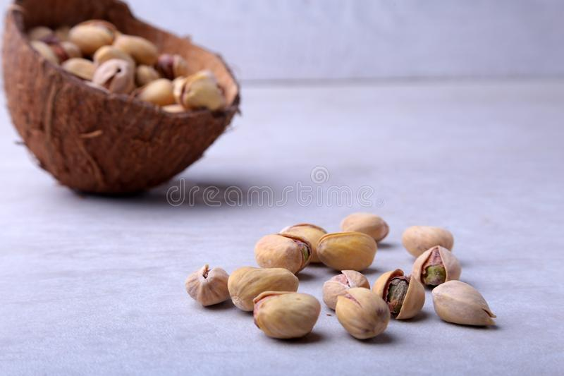 Handmade bowl of coconut with pistachios on a white background. Close-up. royalty free stock images