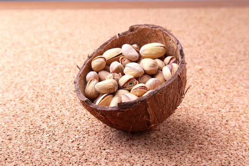 Handmade bowl of coconut with pistachios on a wooden table. Close-up. stock photo