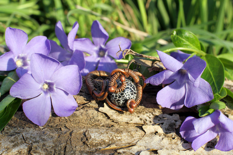 Handmade bronze ring on the nature background. Handmade bronze ring with wood violet in spring on the nature background royalty free stock photos