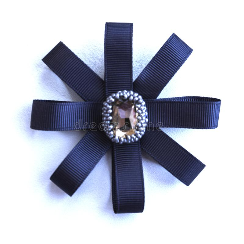 Handmade brooch from dark blue tapes and a rhinestone.  stock photos