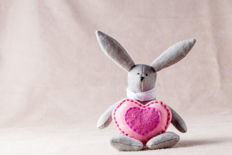 Handmade bunny on soft background. Needlework hobby concept. Handmade bunny with soft heart on soft background stock photography