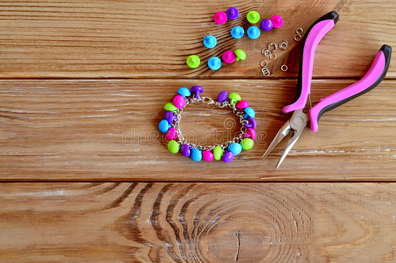Handmade button bracelet. Set of bright colored buttons, pliers. DIY bangle jewelry idea. Easy make creative crafts. Bracelet made out easily available materials stock photography