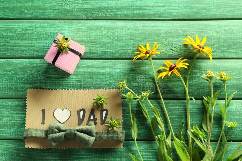 Handmade card with phrase I LOVE DAD, gift box and flowers on color wooden background. Father's day celebration royalty free stock photos