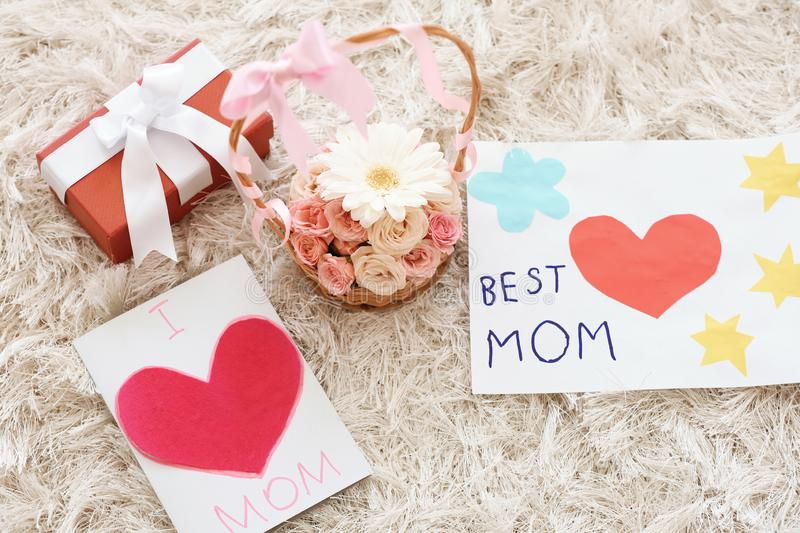 Handmade cards, basket with flowers and gift box on carpet. Mother's day celebration royalty free stock image