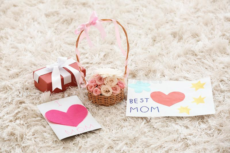 Handmade cards, basket with flowers and gift box on carpet. Mother's day celebration royalty free stock photo