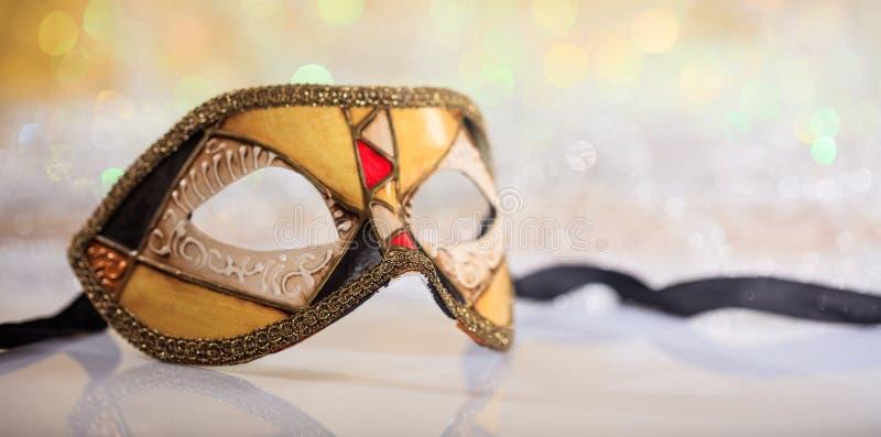 Handmade carnival mask on bokeh background. Handmade venetian carnival mask on white surface, abstract bokeh background stock image