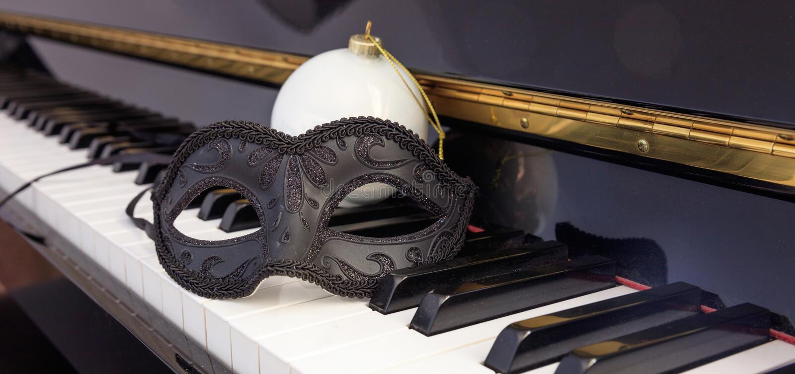 Carnival mask and christmas ball on classical piano keyboard stock images
