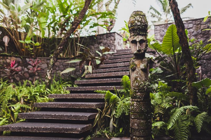 Handmade carved wooden hindu statue in garden. Handmade carved wooden hindu statue in balinese garden royalty free stock photography