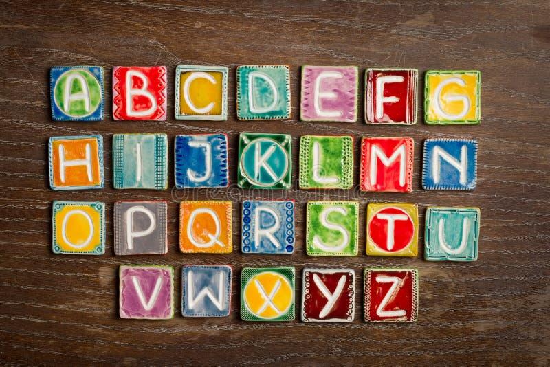 Handmade ceramic alphabet. Colorful handmade ceramic alphabet on wood texture stock photography