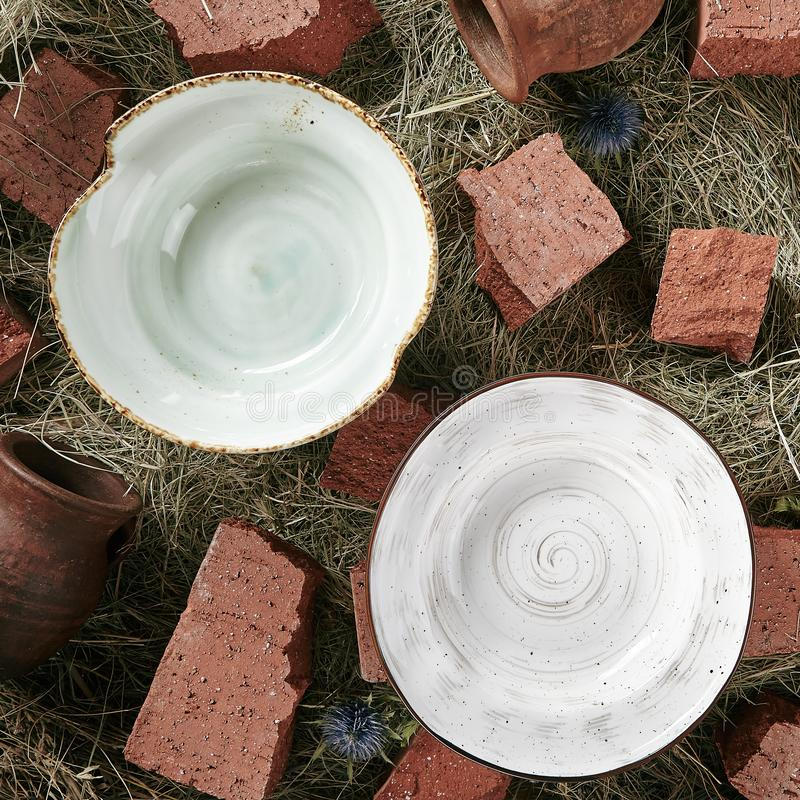 Handmade ceramic plates on old rustic background. With dry straw and broken bricks top view. Set of three white and terracotta blank clay bowls with view from stock image