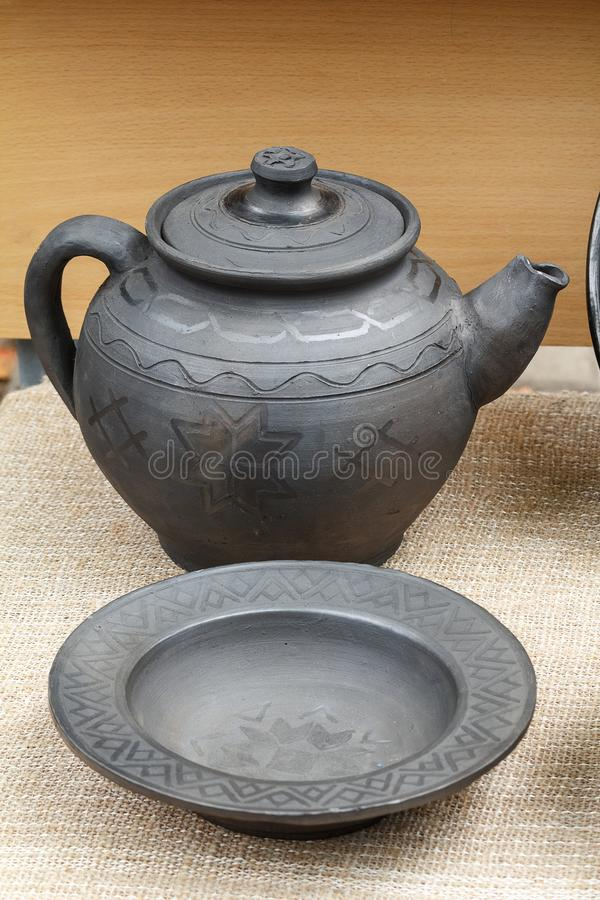 Handmade ceramic teapot and dish. Kettle and dish out of black ceramic for sale at the fair. Belarusian traditional crafts: pottery stock image