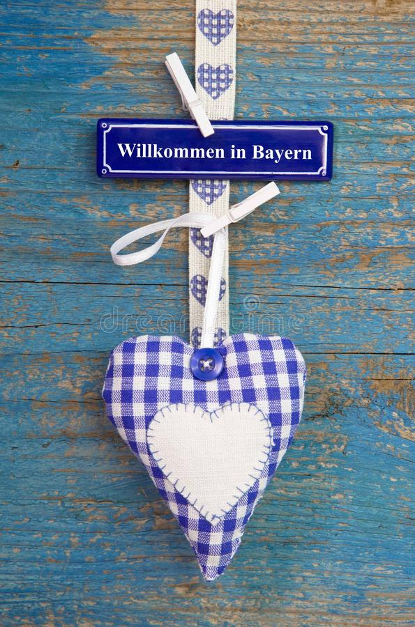 Handmade checkered heart shape against blue wooden surface. royalty free stock images