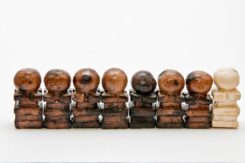 Seven black chess pawns and a white pawn royalty free stock photography
