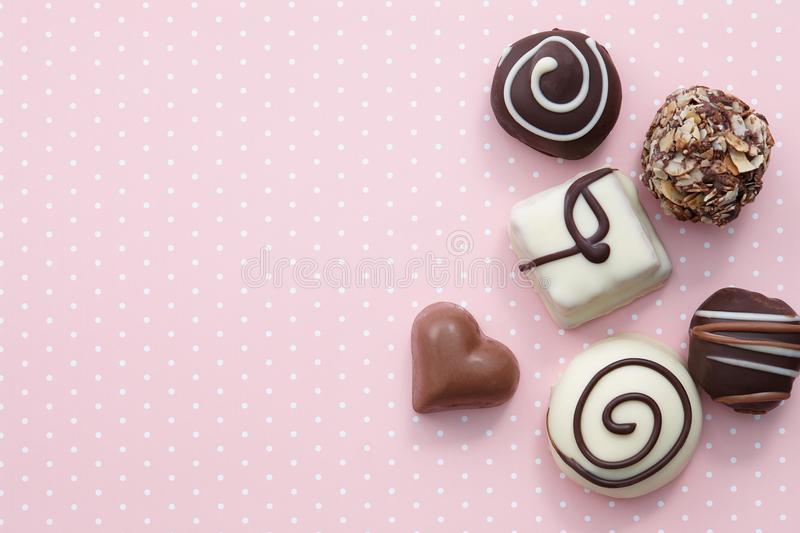 Handmade chocolate candy sweets. On pink background with white dots, top view stock images