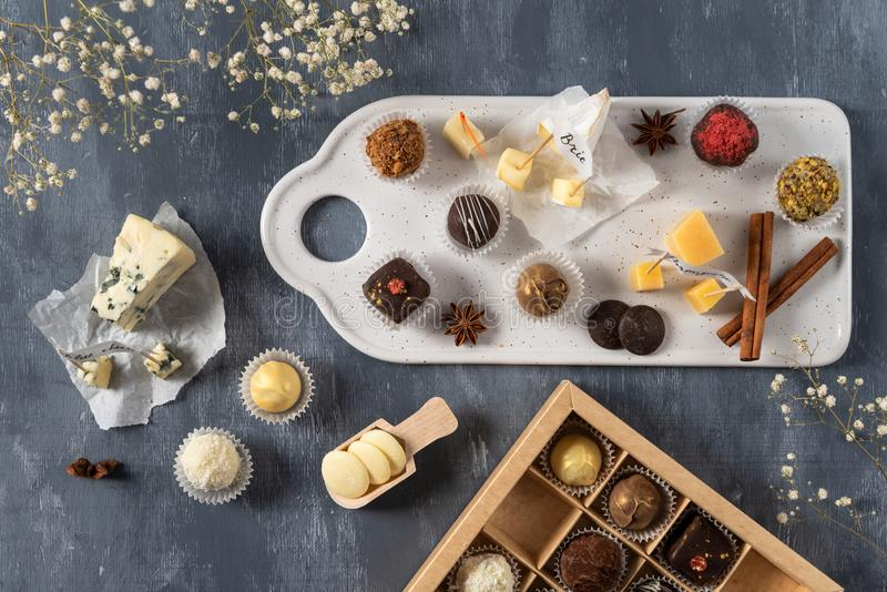 Handmade chocolate cheese candies, white, dark and milk chocolate and different sorts of cheese on the plate. Dessert foe gourmet stock photo