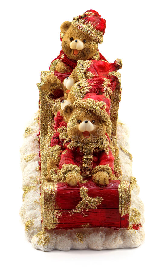 Handmade Christmas bears in sleigh in red and gold jackets and hats on snow isolated. On white stock photos