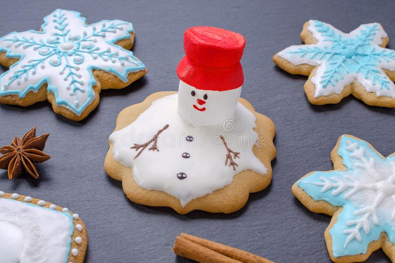 Handmade christmas cookies, melted snowman with red hut and snowflake gingerbread royalty free stock images