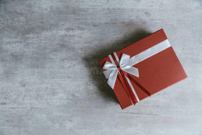Handmade christmas gift or red present box wrapped in kraft paper with a white ribbon on wooden background. Top view, flat lay, c royalty free stock photography