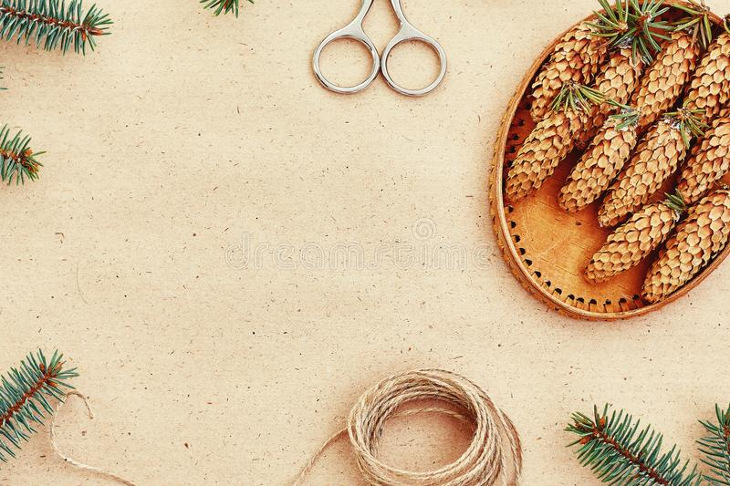 Handmade Christmas gifts, and everything necessary for them, on the Background of Kraft paper, scissors, pine cones and jute cord royalty free stock photo
