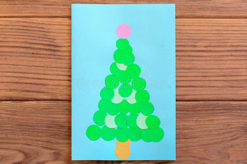 Christmas tree card. Christmas greeting card isolated on a wooden table. Easy thing to make with paper and scissors. Handmade Christmas greeting card. Christmas stock photos