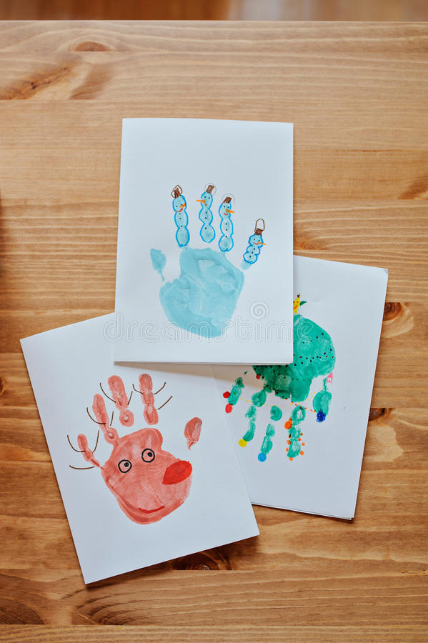 Handmade christmas handprints post cards with deer, snowman and tree. On wooden table royalty free stock image