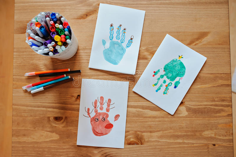 Handmade christmas handprints post cards and pencils on wooden table. Handmade christmas handprints post cards with tree, snowman and deer and pencils on wooden stock images
