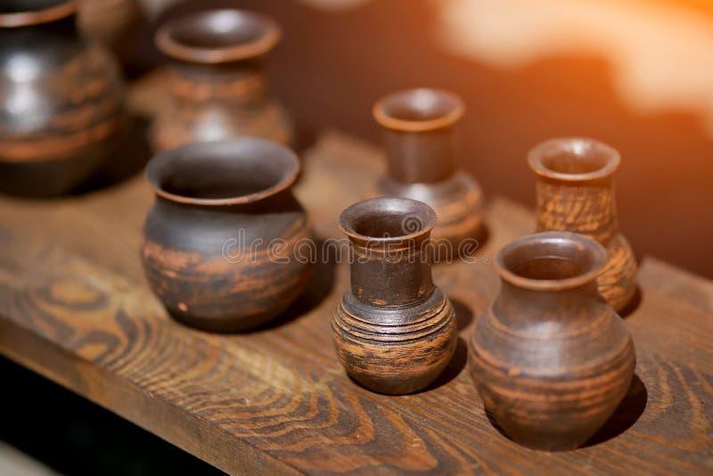 handmade clay pots on wooden table. stock photos