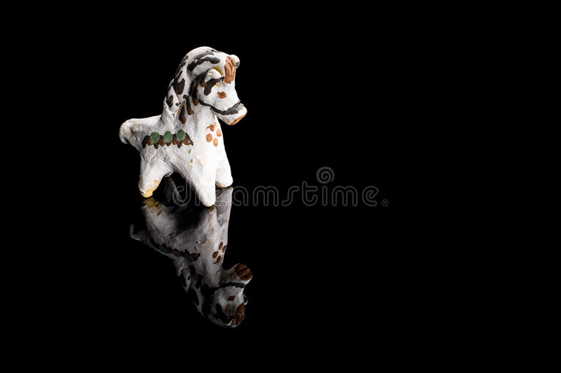 Handmade clay whistle in the form of a horse. Painted with ukrainian tracery, on black reflecting background royalty free stock images