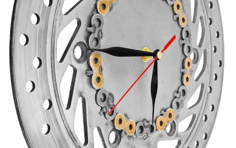 Handmade clock made of motorcycle parts. A clock face made of a. Brake disc decorated with hand-painted chain parts. Artistic object on a white background stock photo