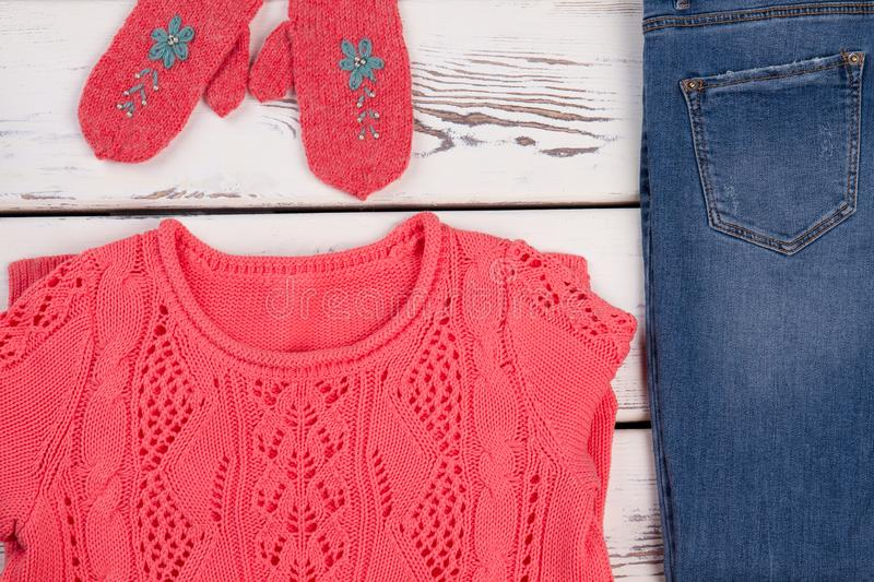 Handmade clothes and denim pants. For teenage girls. Set of knitted sweatshirt and cute gloves for cold weather stock photos