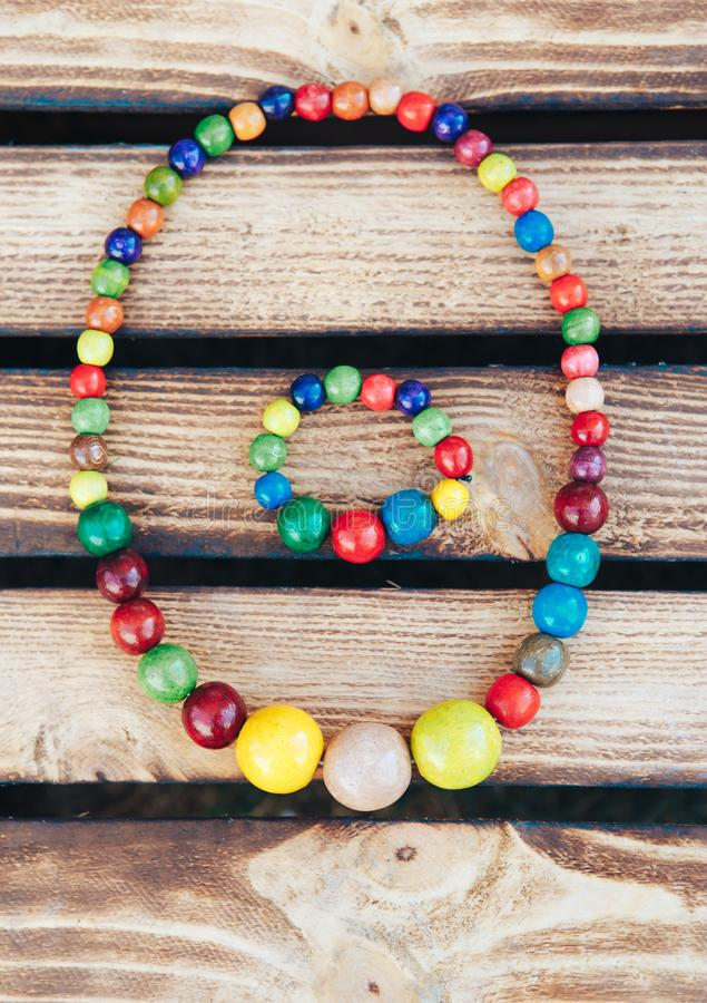 Handmade Colored Jewelry. Colored beads and wood bracelet. Wooden background stock image
