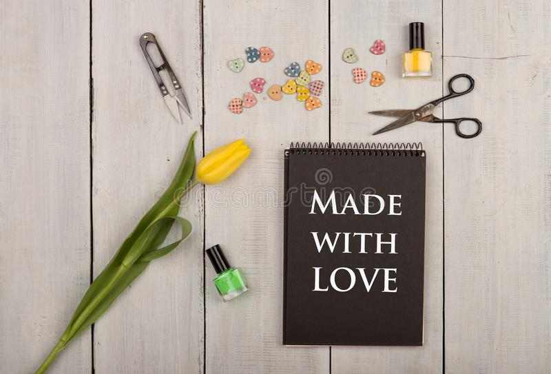 Handmade concept - flower tulip, black note pad with text Made with love, sewing scissors, nail polish and buttons in the shape of royalty free stock photos
