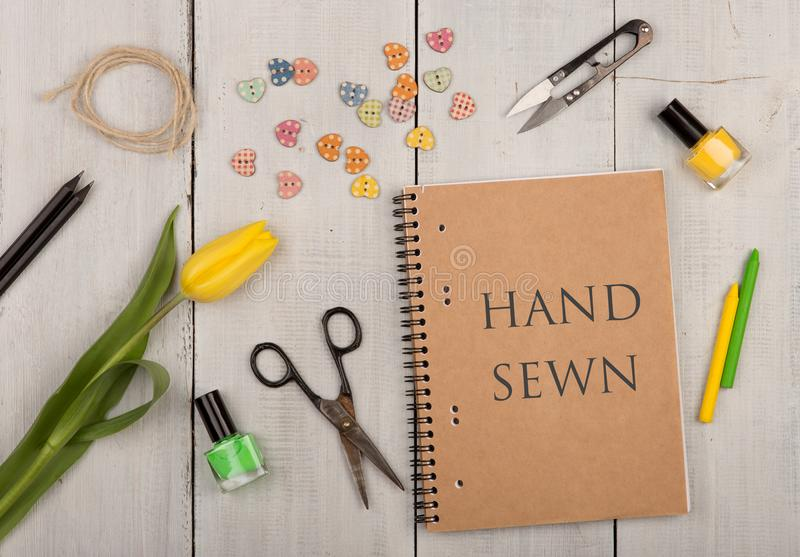 Handmade concept - sewing scissors, tulip, eco note pad with text Hand sewn, nail polish and buttons in the shape of hearts. On a white wooden table, workshop royalty free stock photos