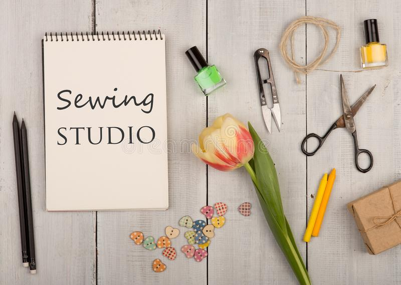 Handmade concept - sewing scissors, tulip, eco note pad with text Sewing studio, gift box, nail polish and buttons in the shape of. Hearts on a white wooden royalty free stock images