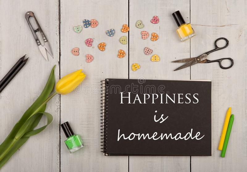 Handmade concept - tulip, black note pad with text Happiness is homemade, sewing scissors, nail polish and buttons in the shape of royalty free stock images