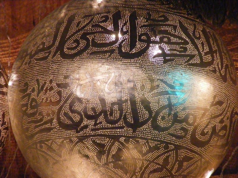 Shining Arabic copper lantern in khan el khalili souq with Quran arabic handwriting engraved on it. Handmade copper golden lantern lamps with arabic handwriting royalty free stock photos