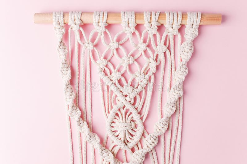A handmade 100% cotton macrame wall decoration hanging on pink wall. Decoration for the interior. Trendy handcrafted decor for stock photo