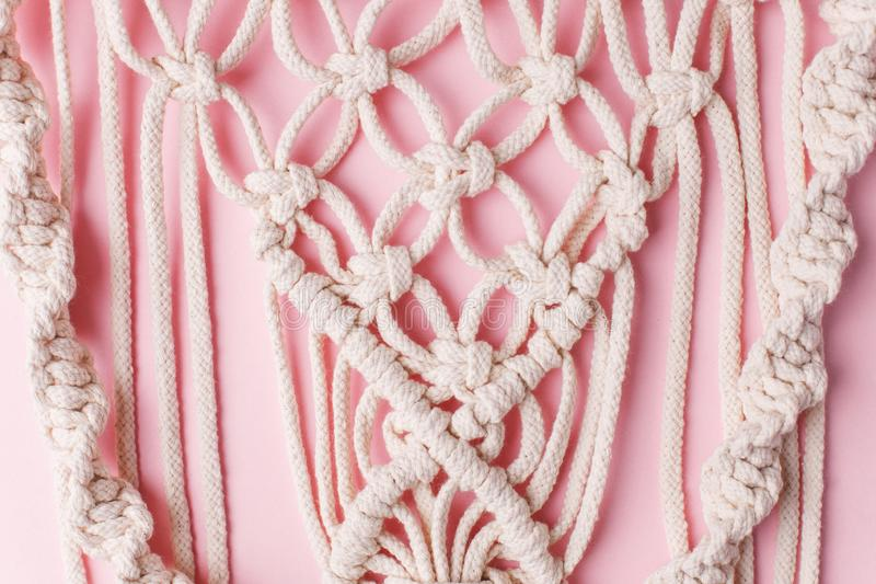 A handmade 100% cotton macrame wall decoration hanging on pink wall. Decoration for the interior. Trendy handcrafted decor for. House stock photos