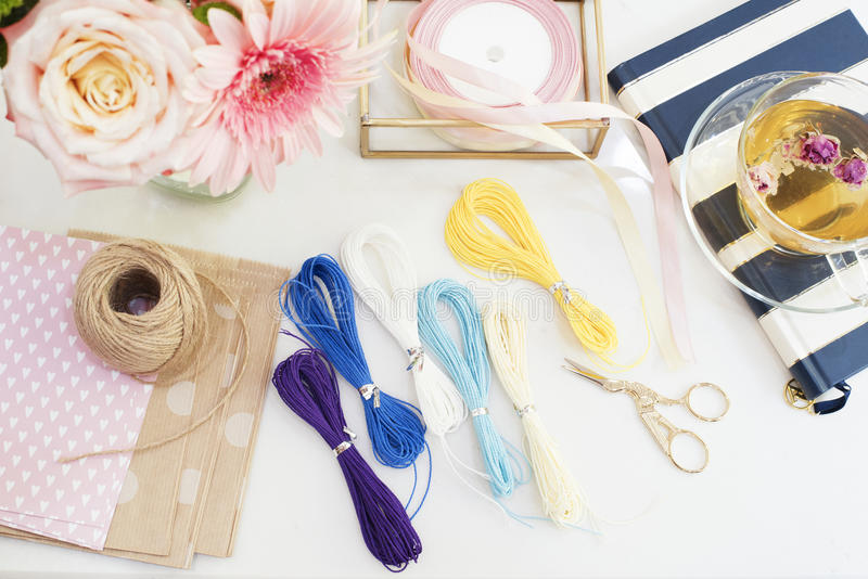 Handmade, craft concept. Materials for making string bracelets and handmade goods packaging - twine, ribbons. Feminine workplace c. Oncept. Freelance fashion stock photography