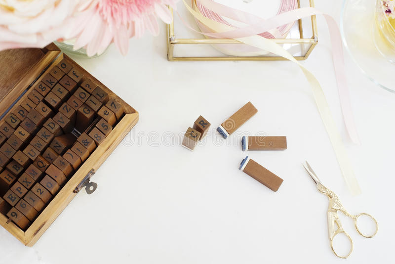 Handmade, craft concept. Wooden rubber stamps, golden scissors, ribbons. Feminine workplace concept. Freelance fashion femininity. Workspace in flat lay style stock image