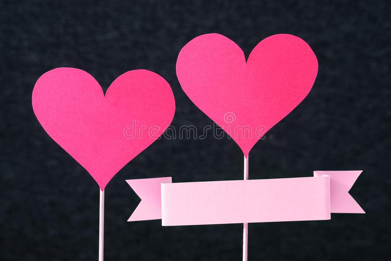 Handmade craft design for mother`s, valentine`s or women`s day. Card. 2 red hearts and empty ribbon with copy space cut from cardboard or paper on a wooden royalty free stock images