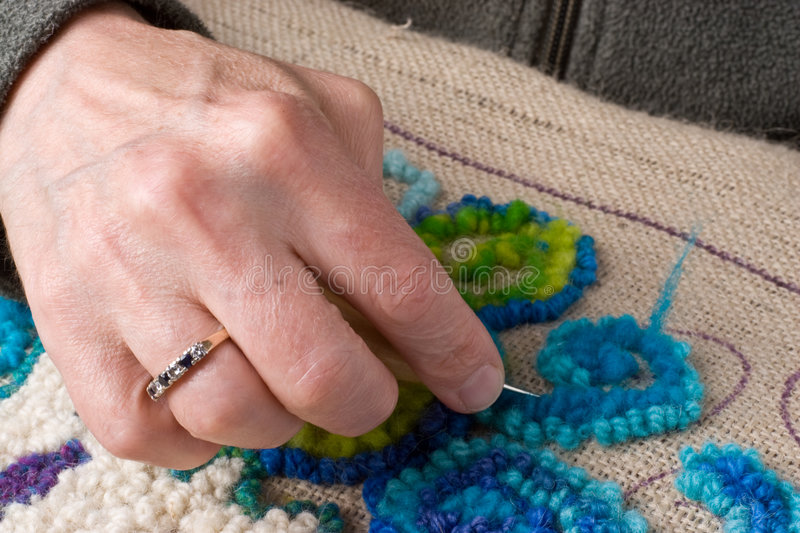 Handmade craft: Rug Hooking. Detail showing a hand hooking a rug, a traditional maritime craft that recyles old fabrics into vibrant mats using burlap royalty free stock images