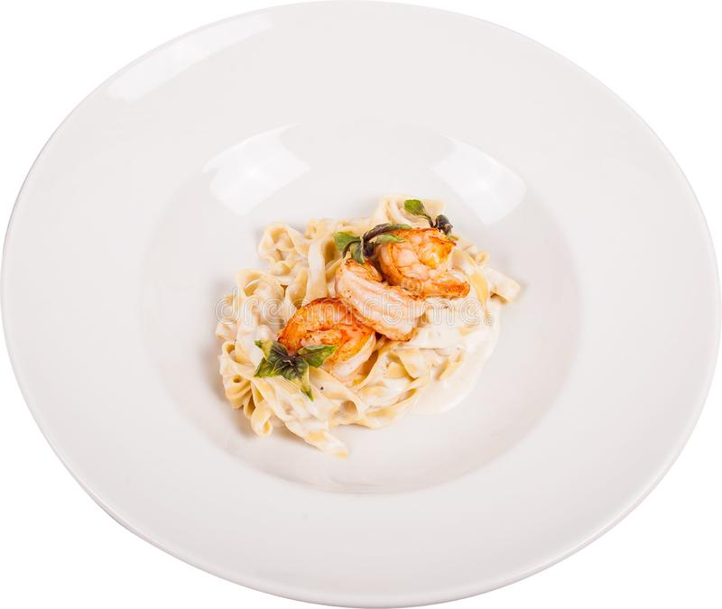 Handmade creamy pasta cooked on a shrimp biscuit, flavored with lemon pepper. Served with tiger prawns fried in aromatic herbs on stock photography