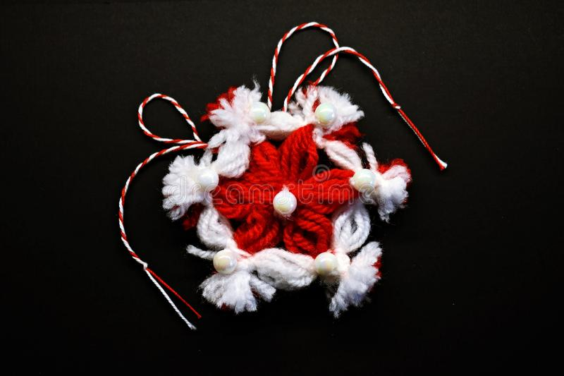 Handmade crocheted flower with red and white string, known as Martisor. stock photos