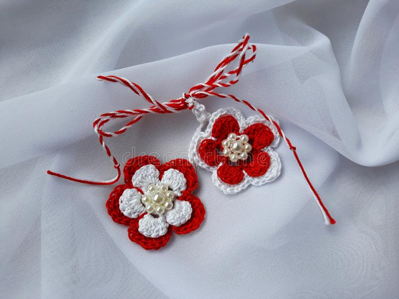 Handmade crocheted flowers with red and white string, known as Martisor. royalty free stock photography