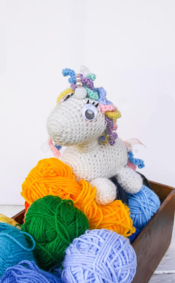 Handmade crocheted unicorn toy and yarn in a wooden box on white background. stock photos