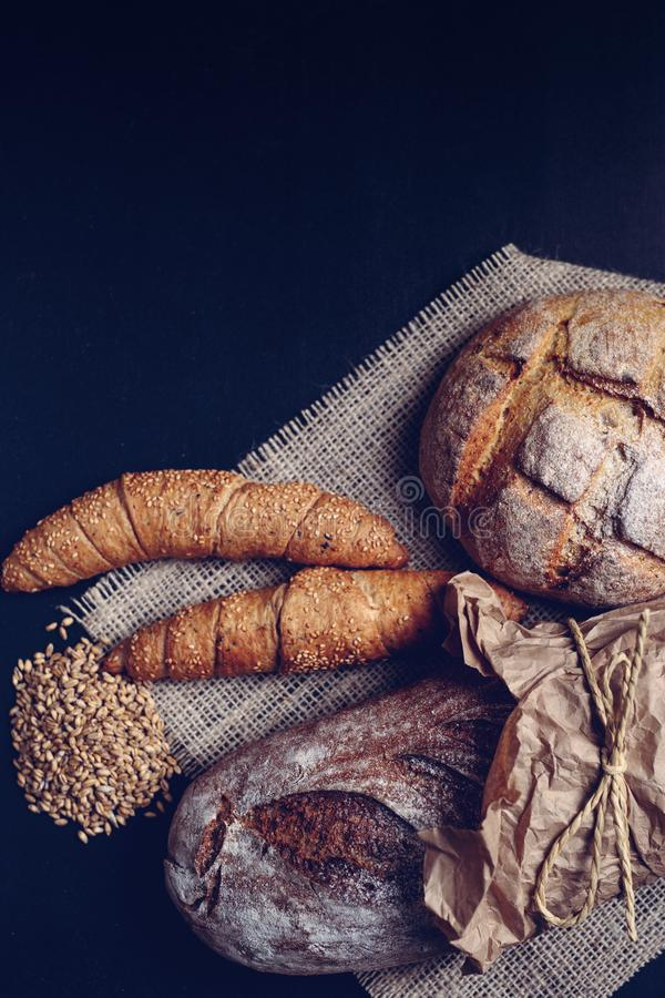 Handmade croissant and two loaves of dark bread stock photo